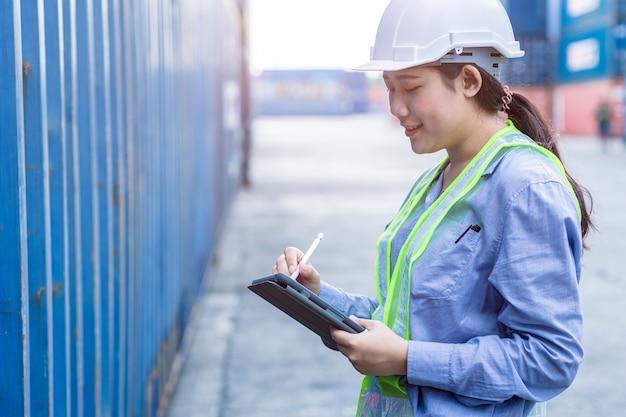 Штатный работник-женщина счастлива, работая в зоне погрузки груза логистики груза, используя беспроводную технологию планшета для проверки таможенной детали кода импортно-экспортного контейнера.