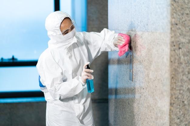 파란색 살균제 병이있는 엘리베이터 푸시 버튼 제어판 청소 닦기를 사용하여 방호복에서 일하는 여성 직원