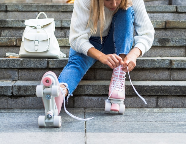 Woman on stairs tying shoelaces on roller skates