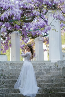 Woman on the stairs under a wisteria tree with lilac flowers