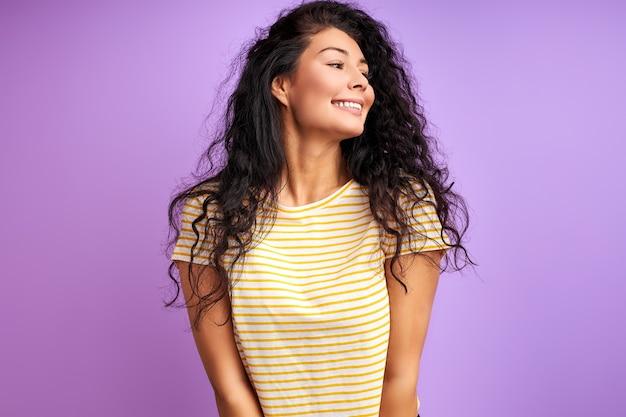여자는 보라색 벽 위에 절연, 행복으로 빛난다.