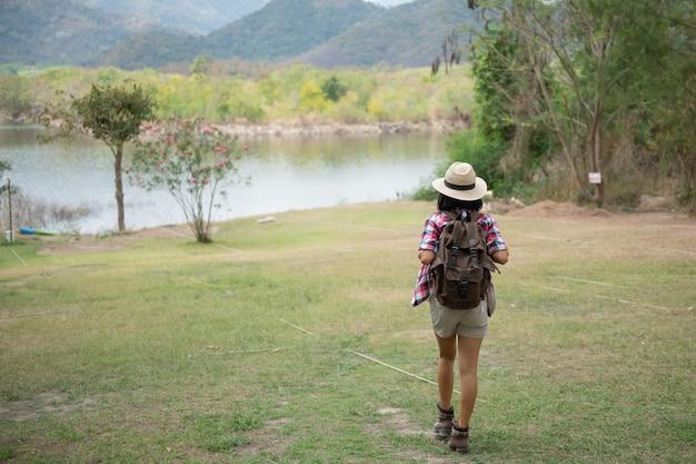 여자는 호수의 은행에 서 / 아시아 여자 등산객 앞에 웃 고 행복, 숲에서 하이킹하는 여자, 따뜻한 여름날.