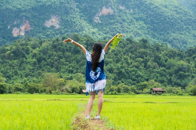Woman stand on rice field on morning with flare at pa bong piang, chiang mai, thailand.