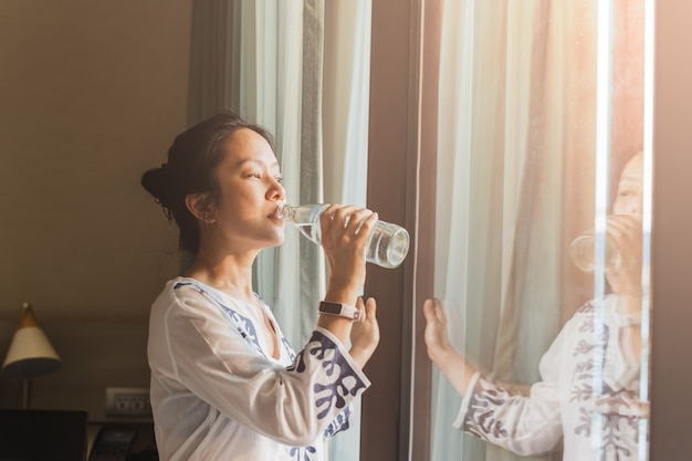 Woman stand next to window drinking water from bottle in nature light.