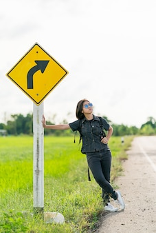 Woman stand with backpack hitchhiking along a road