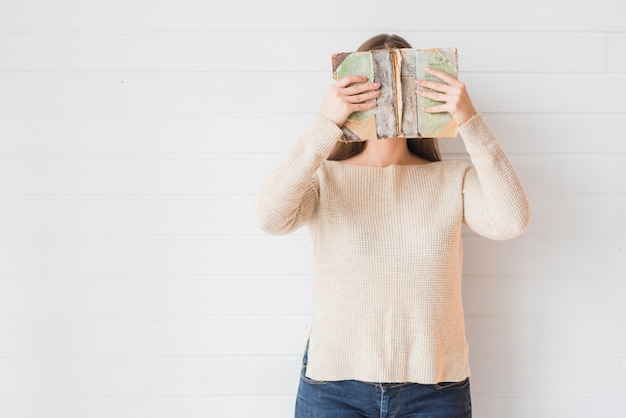 Woman standing against wall covering her face with book