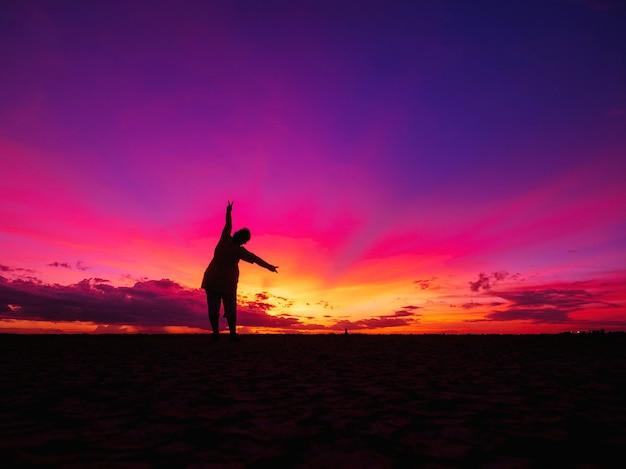 美しい夕日の中で太陽に面したフィールドに一人で立っている女性。