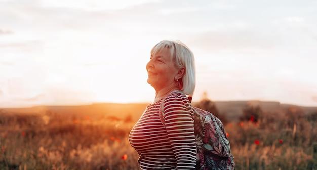 Woman standing alone raising hands enjoying sunset outdoors