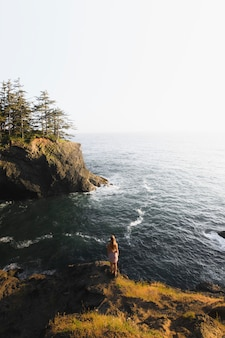 Woman standing alone on a seacliff