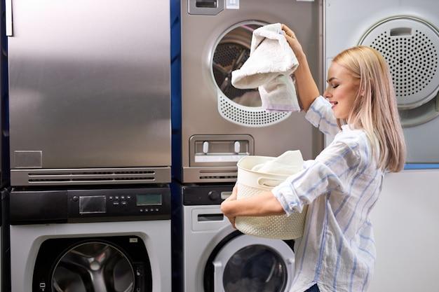 Женщина, стоящая одна с чистой одеждой в прачечной самообслуживания с сушильными машинами. женщина в повседневной одежде стоит, держа таз с одеждой, счастливая после получения чистых полотенец