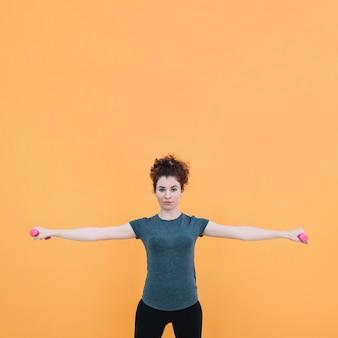 立って、ダンベルで運動する女性