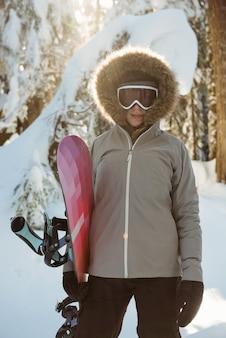 立ってスノーボードを持っている女性