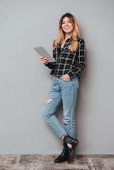 Женщина стоит и держит планшетный компьютер на сером фоне