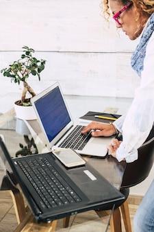 机の上で事務作業をしながら立ってノートパソコンのキーボードを操作している女性。自宅やオフィスの職場で2台のラップトップで忙しい女性フリーランサー
