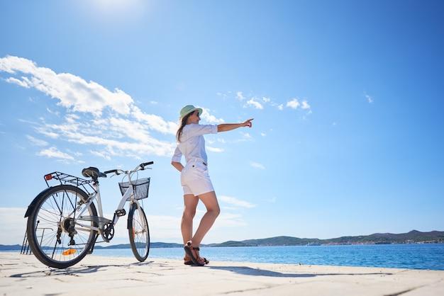 Женщина, стоящая на велосипеде на каменистом тротуаре под ясным голубым небом, указывая на противоположном берегу на фоне сверкающей чистой воды