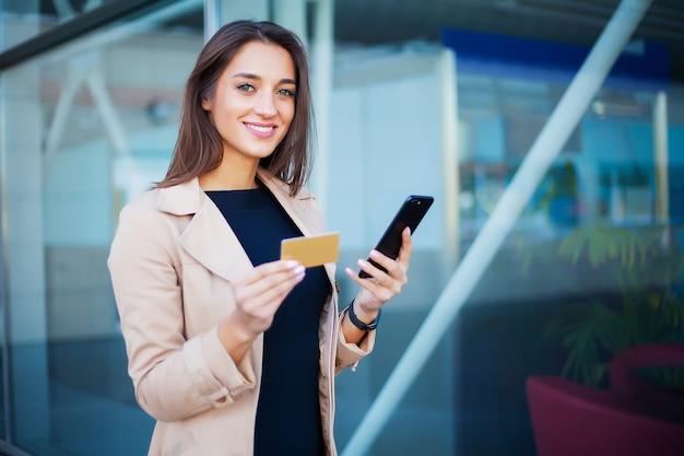 空港のホールに立っている女性彼は支払いにゴールドのクレジットカードと携帯電話を使用しています