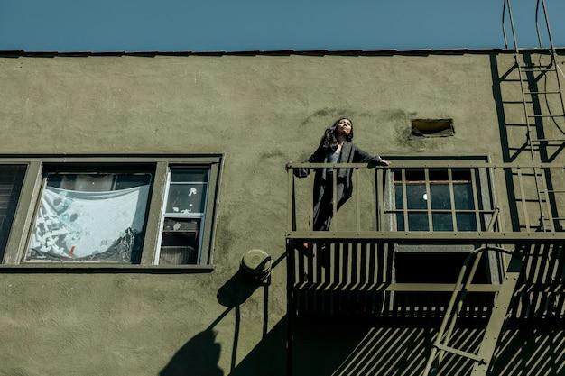 코비드-19 전염병 동안 la 시내에 있는 자신의 아파트 화재 탈출구에 서 있는 여성.