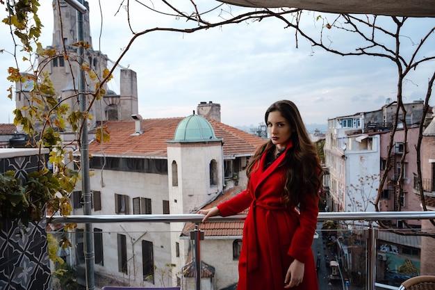 Женщина, стоящая в кафе на крыше с стамбулом на фоне, вид на башню галата в бейоглу, турция. путешествие и отдых в турции концепции