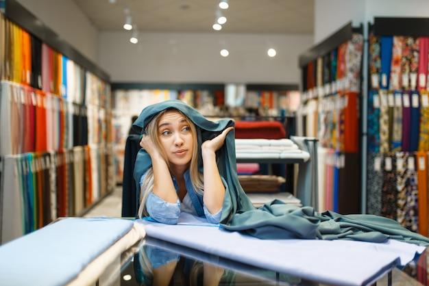 繊維店のショーケースに立っている女性。