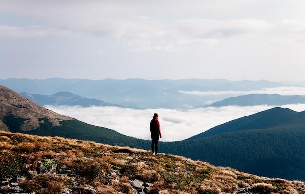 Женщина, стоящая на вершине горы, удивительный пейзаж в горах