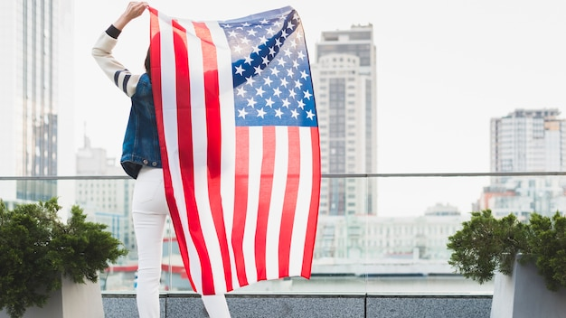 Woman standing on balcony with big american flag