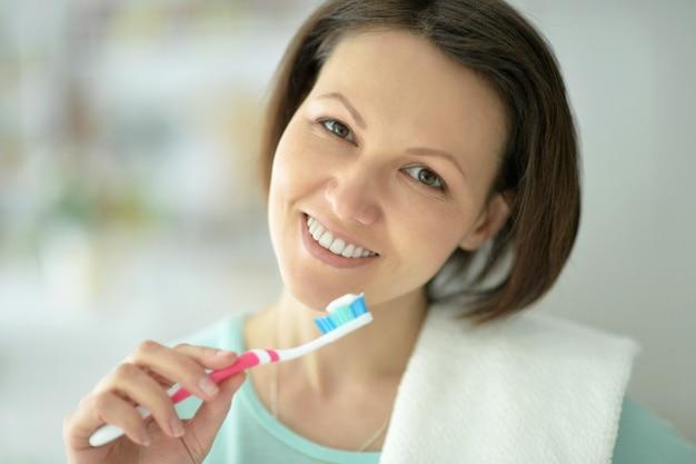 Woman standing in  bathroom and brushing her teeth.