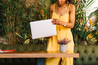 Woman standing behind the wooden table holding laptop in hand