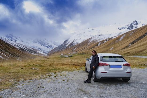 이탈리아 파소 델로 스텔비오(passo dello stelvio)의 풍경을 바라보며 차 옆에 서 있는 여성