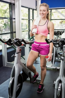 Woman standing beside exercise bike