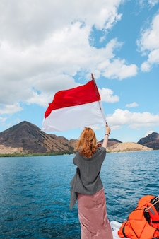 A woman standing on a boat and waving indonesia flag in the middle of sea