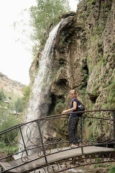 Woman standing on bridge looking at the beautiful mountain waterfall
