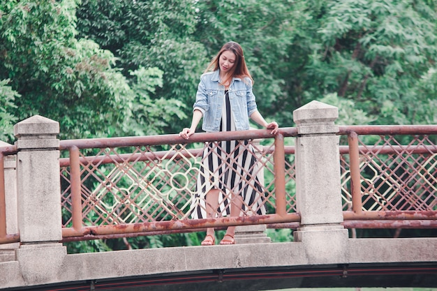 Woman standing on the bridge in the park