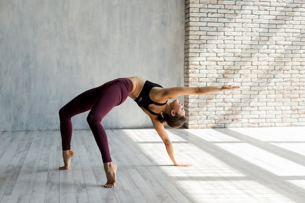 Woman standing in bridge pose with arm extended