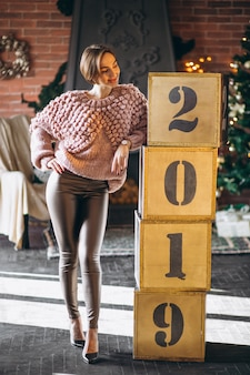 Woman standing by boxes 2019 on christmas