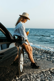 Woman standing by car with juice bottle