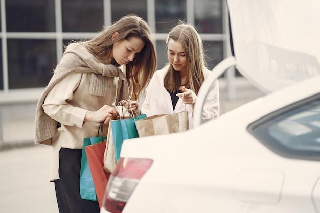 買い物袋が付いている車で立っている女性