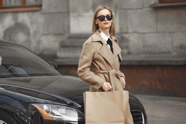 Женщина стоит у машины с сумками