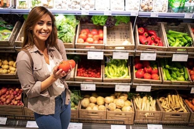野菜だらけの棚のそばに立ってトマトを持っている女性。