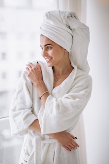 Woman standing by the window in bathrobe