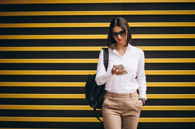 Woman standing by the yellow wall and talking on the phone