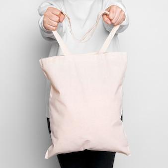 Donna in piedi e portando una tote bag