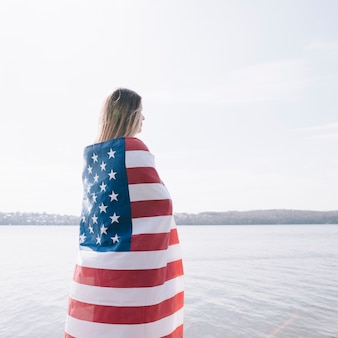 Woman standing completely wrapped in american flag and looking at sea