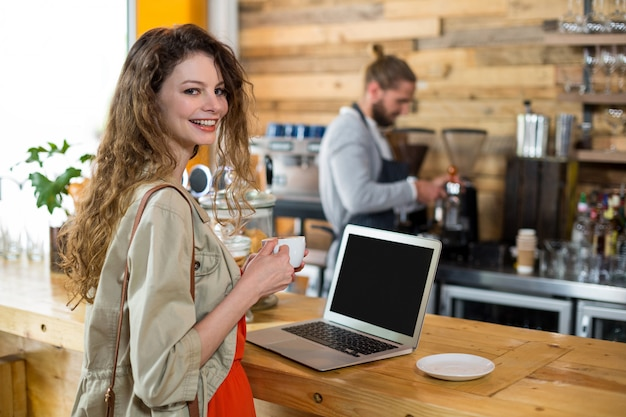 Woman standing at counter and using laptop while having coffee in coffee