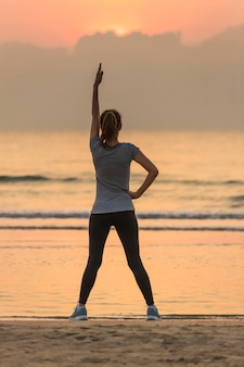 Woman standing and exercise on beanch in the morning with colorful sky and wave in background.