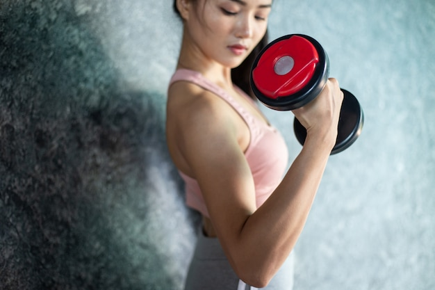 Woman standing exercising with a red dumbbell in the gym.