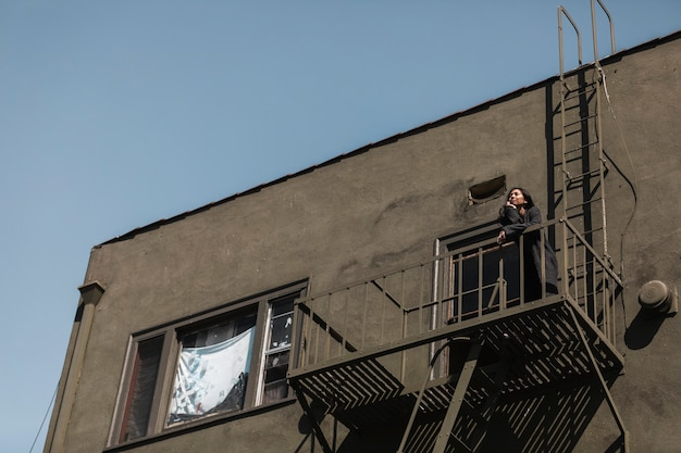 Woman standing on fire escape during the coronavirus lockdown
