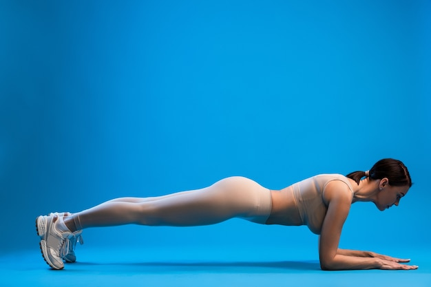 Woman standing in forearms plank pose on blue wall
