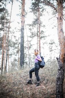 Donna in piedi sulla collina della foresta