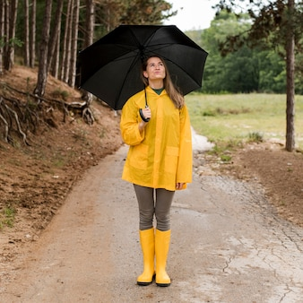 Woman standing in the forest while holding an umbrella