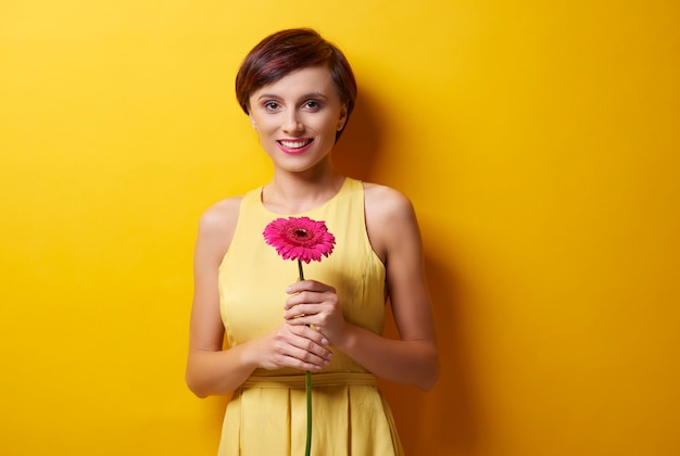 Woman standing in front of camera with flower